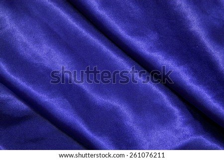 blue background abstract cloth of wavy folds of silk texture satin or velvet material or design of elegant curves blue material