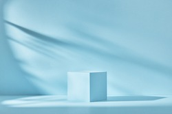 Blue background for product presentation with shadows and light. Empty cubic podium. Mockup.