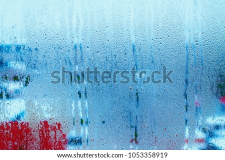 Blue background of natural water condensation, window glass with high air strong humidity, large drops drip. Collecting and streaming down