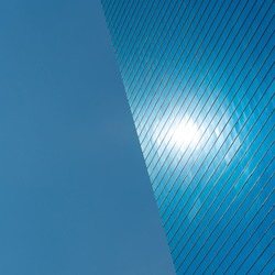 Blue background. The left side is blue sky, the right half is a modern blue glass office building with a spot that is reflection of the sun. Space for text. Fine for placing logo in the center