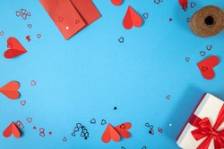 Blue background with gift, envelope and papper hearts. Present with love symbols on the sides with copy space in center. Valentine theme from above in flat lay composition.