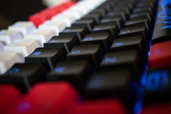 Blue Backlit Mechanical Keyboard with black, white, red keycaps at an angle