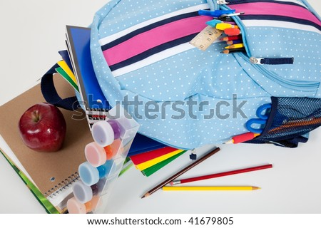 Blue backpack full of supplies including paints, pencils, notebooks, text books, scissors, folders and an apple on a white background