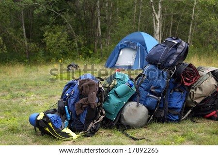 Blue backpacking bags piled up in a line at the campsite