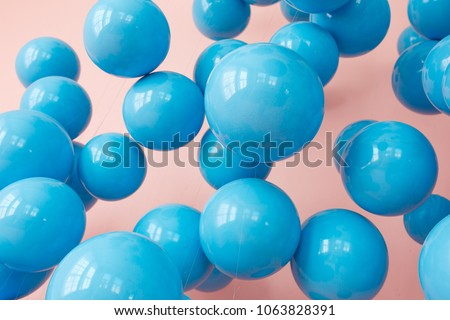 blue balloons, blue bubbles on pink background. Modern punchy pastel colors. Close up shot with shiny reflection