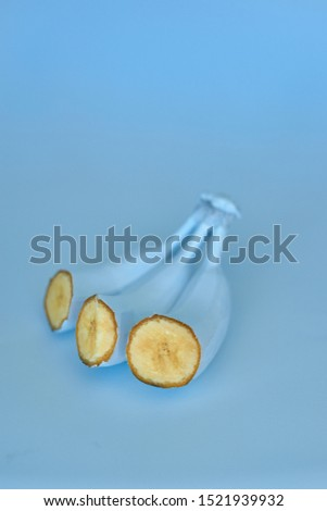 Blue bananas on a blue background. Minimal style. GMO concept. sectional view