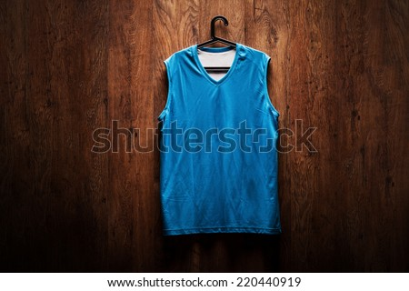 Blue basketball jersey hanging on a wooden wall on a hanger