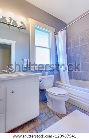 Blue bathroom with white cabinets with stone tiles and blue tiles. - stock photo