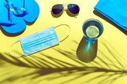 BLUE BEACH ACCESSORIES AND PROTECTIVE MASK ON YELLOW BACKGROUND. SUMMER HOLIDAYS CONCEPT WITH CAUTION FOR CORONAVIRUS. TOP VIEW.