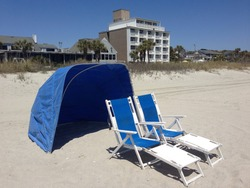 Blue beach chairs and sun / wind tent waiting for you.