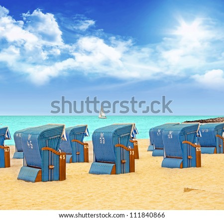 blue beach chairs on sandy underground at the baltic sea - stock photo