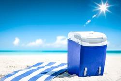 Blue beach fridge on sand and ocean landscape. Summer sunny day.