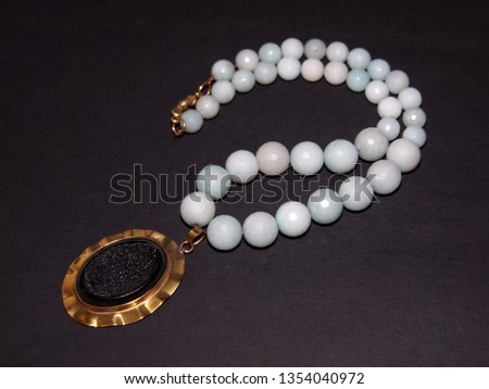 Blue beads necklace isolated on a dark background #1354040972
