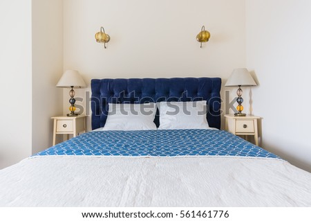 blue bed with soft headboard and bedside console with lamp #561461776