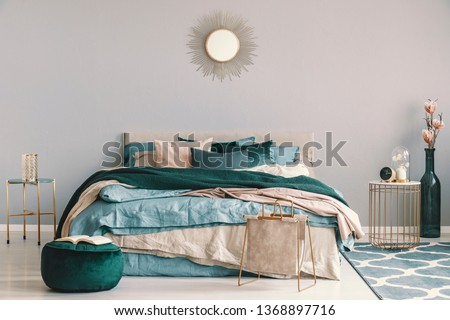 Blue, beige and emerald green bedding on king size bed in contemporary bedroom interior with golden accents