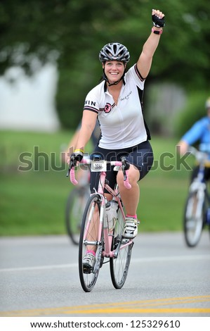 BLUE BELL, PA - AUGUST 19: A rider raises her arm celebrating her completion of a ride in the Livestrong Challenge event August 19, 2012 in Blue Bell, PA.
