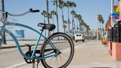 Blue bicycle, cruiser bike by ocean beach, pacific coast, Oceanside California USA. Summertime vacations, sea shore. Vintage cycle by beachfront house, waterfront cotteges, bungalow huts and palm tree