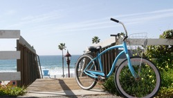 Blue bicycle, cruiser bike by ocean beach, pacific coast, Oceanside California USA. Summertime vacations sea shore. Vintage cycle by wooden stairs, stairway or staircase. Tropical palms and lifeguard