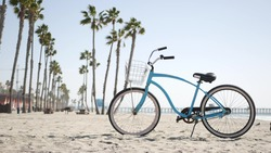 Blue bicycle, cruiser bike by sandy ocean beach, pacific coast near Oceanside pier, California USA. Summertime vacations, sea shore. Vintage cycle, tropical palm trees, lifeguard tower watchtower hut