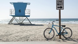 Blue bicycle, cruiser bike by sandy ocean beach, pacific coast, Oceanside California USA. Summertime vacations, sea shore. Vintage cycle by road sign One Way. Lifeguard tower, rescue watchtower hut.