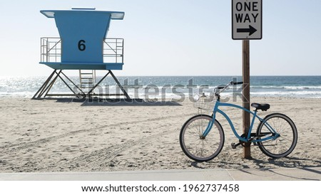 Blue bicycle, cruiser bike by sandy ocean beach, pacific coast, Oceanside California USA. Summertime vacations, sea shore. Vintage cycle by road sign One Way. Lifeguard tower, rescue watchtower hut. Foto stock ©