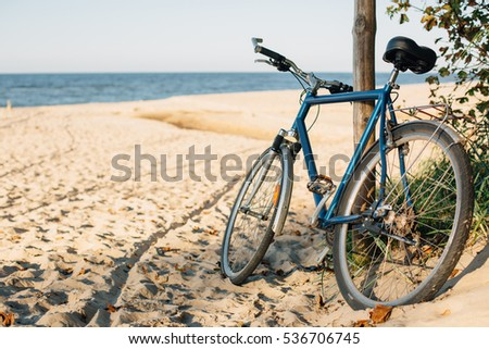 Photo of Blue bicycle parked near the sea standing on the beach.