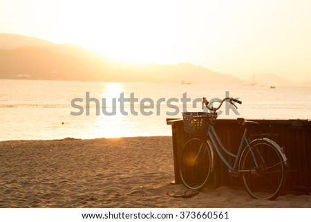 Blue bicycle standing on sandy beach during sunrise. Freedom and happiness concept. Old fashioned sepia colors. Post card view.