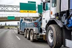 Blue Big rig industrial powerful tow semi truck towing broken semi truck on the lifting boom driving on the wide highway road with road signs and bridge to repair shop point