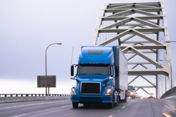 Blue big rig powerful excellent for long-distance industrial transportation semi truck with turn on headlight transporting semi trailer running on arched Fremont bridge in Portland