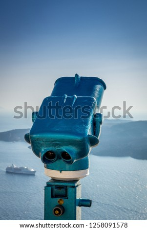 blue binoculars and cruiseship in summertime on the island of Santorini in Greece. Binoculars, view, cruise, summer, holiday, luxury travel concepts.