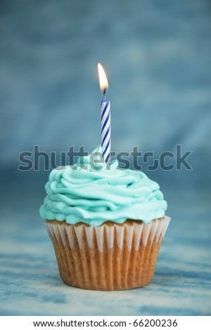 Blue birthday cake with candle on a blue background