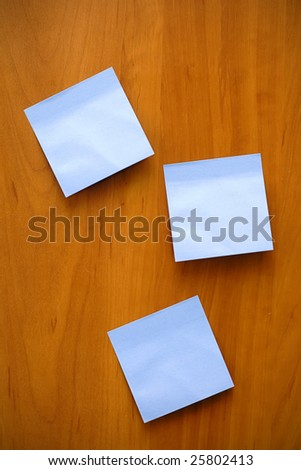 blue blank sticky note on wooden background. texture
