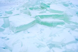 blue blocks of ice on the pond. ice-floes were piled during cutting