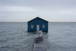 Blue boat house on the Swan River in Perth. Blue boat shed in Storm from cyclone mangga. Perth, Western Australia