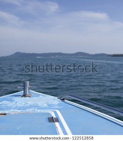 blue boat sailing in the sea against blue sky - stock photo