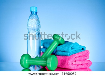 Blue bottle of water, sports towel, measure tape and dumbbells on blue background