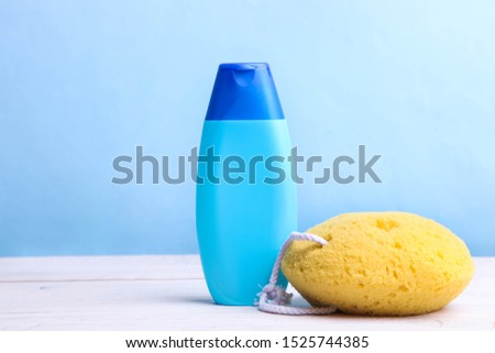 Blue bottle with shampoo or shower gel and sponge on blue background. Copy space. Copy space.