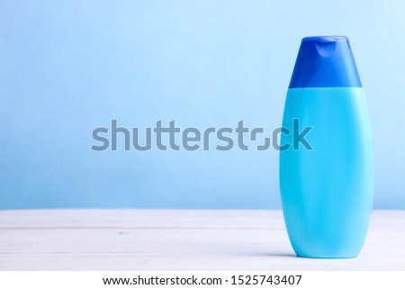 Blue bottle with shampoo or shower gel on blue background. Copy space. Copy space.