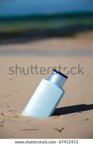 Blue bottle with Sunblock lotion in sand on a beach, outdoor