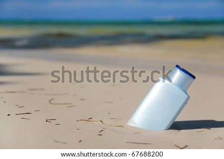 Blue bottle with Sunblock lotion in sand on tropical beach, outdoor