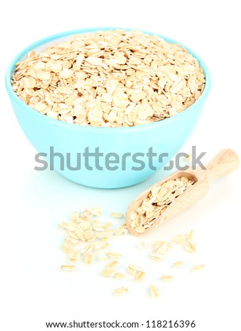 Blue bowl full of oat flakes with wooden scoop isolated on white