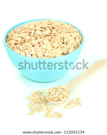 Blue bowl full of oat flakes with wooden spoon isolated on white - stock photo