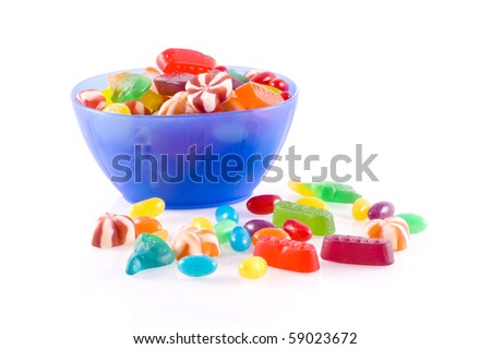 Blue bowl with different kinds of colorful candy isolated on white.