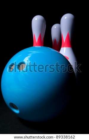 blue bowling ball and bowling pins