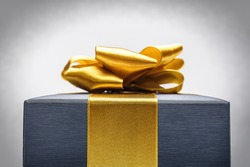 Blue box gift tied with gold ribbon with a bow