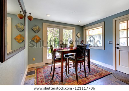 Blue bright dining room with red rug and high table.