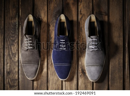 Blue, Brown and Gray Suede Shoes on a Wooden Background.