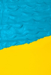 Blue Brush waves strokes paint on yellow isolated paper background. Minimal abstract creative wallpaper. Ocean and sand vacation vibes