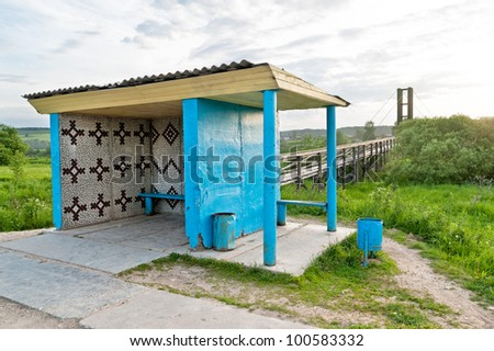 Blue bus stop with garbage cans against hanging wooden footbridge with rails in background.  Arkhangelsky region, Russia.