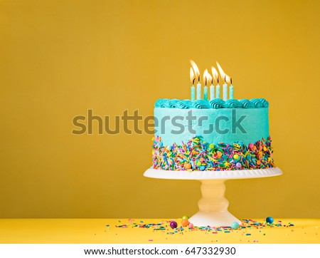 Blue buttercream birthday cake with colorful sprinkles over yellow background.